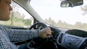 Отснятый видеоматериал замедленного движения молодого человека начиная и управляя автомобиль на дороге сельской местности сток-видео