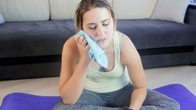 Отснятый видеоматериал замедленного движения очень уставшей потной женщины обтирая ее лоб после делать тренировки фитнеса видеоматериал