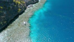 Отснятый видеоматериал круга воздушный шлюпок banca отключения туристских отдыхая над коралловым рифом около святыни Matinlok Nid видеоматериал