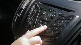 Отснятый видеоматериал крупного плана замедленного движения женской руки регулируя уровень звука радио на системе multemedia авто акции видеоматериалы