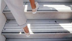 Отснятый видеоматериал крупного плана 4k женских ног в тапках идя вверх по лестнице к приземляться в самолет видеоматериал