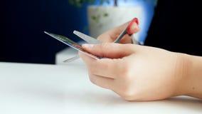 Отснятый видеоматериал крупного плана 4k кредитной карточки женского вырезывания работника банка пластичной с ножницами видеоматериал