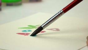 отснятый видеоматериал Медленн-mo Рука девушки художника рисуя акварель с щеткой Конец-вверх видеоматериал