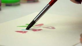 отснятый видеоматериал Медленн-mo Рука девушки художника рисуя акварель с щеткой Конец-вверх акции видеоматериалы