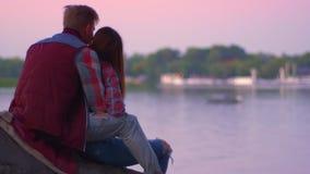 Отснятый видеоматериал от заднего og обнимая прекрасных пар, сидя и смотря красивый вид реки и острова далеко за пределы, спокойн акции видеоматериалы