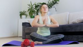 Отснятый видеоматериал тележки 4k молодой женщины сидя в представлении йоги лотоса на циновке фитнеса дома сток-видео
