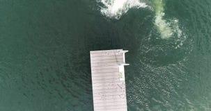 Отснятый видеоматериал трутня 3 вышколенных людей скача в воду, на открытом воздухе в утре сток-видео