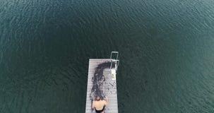 Отснятый видеоматериал трутня 3 вышколенных людей скача в воду, на открытом воздухе в утре акции видеоматериалы