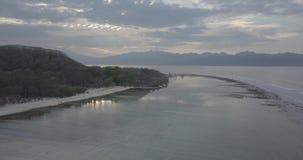 Отснятый видеоматериал трутня спокойного рассвета на получившемся отказ пляже изумляя остров Gili, Индонезию акции видеоматериалы