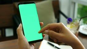 отснятый видеоматериал 4k близкая поднимающая вверх рука женщины держа умный хон с зеленым экраном на кофейне, пальце скольжения  видеоматериал
