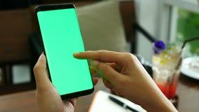 отснятый видеоматериал 4k близкая поднимающая вверх рука женщины держа умный телефон с зеленым экраном на кофейне, используя каса