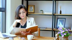 отснятый видеоматериал 4K, красивая азиатская бизнес-леди сидя перед компьтер-книжкой компьютера, чтение и сальто над страницей и акции видеоматериалы