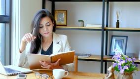 отснятый видеоматериал 4K, красивая азиатская бизнес-леди сидя перед компьтер-книжкой компьютера, чтение и сальто над страницей б сток-видео