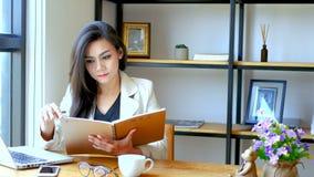 отснятый видеоматериал 4K, красивая азиатская бизнес-леди сидя перед компьтер-книжкой компьютера, чтение и сальто над страницей б видеоматериал