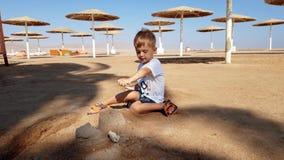 отснятый видеоматериал 4k меньшего замка песка здания мальчика малыша на пляже акции видеоматериалы