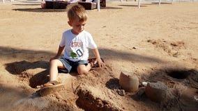 отснятый видеоматериал 4k меньшего мальчика малыша сидя на пляже моря и строя замке от влажного песка акции видеоматериалы