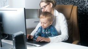 отснятый видеоматериал 4k молодой коммерсантки работая в офисе с ее милым усмехаясь мальчиком малыша сток-видео