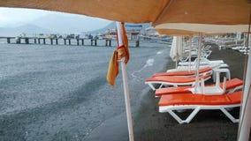 отснятый видеоматериал 4k пустого пляжа с влажными sunbeds на пляже во время большого дождя Концепция избалованных каникул Плохая сток-видео