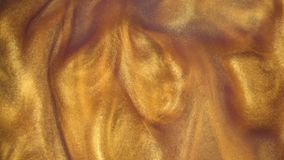 отснятый видеоматериал 4k Чернила в воде Чернила золота реагируя в воде создавая абстрактную предпосылку сток-видео