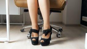 отснятый видеоматериал 4k элегантной коммерсантки нося длинные пятки сидя в стуле офиса акции видеоматериалы