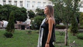 отснятый видеоматериал 4k элегантной молодой женщины в черном платье идя в парк сток-видео