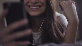 Отснятый видеоматериал конца-вверх замедленного движения молодой женщины лежит в кровати и использует smartphone, девушку слушает видеоматериал