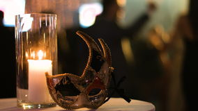 Отснятый видеоматериал конца-вверх свечи включения в стеклянной чашке и масленица маскируют налево на таблице в клубе, людях танц сток-видео