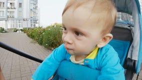 Отснятый видеоматериал крупного плана замедленного движения милого младенца в трясти pram головной и делать стороны видеоматериал