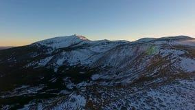 Отсталое воздушное взгляд сверху над горой зимы снежными и лесом древесин на заходе солнца или восходе солнца Голубые сумрак или  акции видеоматериалы