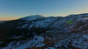 Отсталое воздушное взгляд сверху над горой зимы снежными и лесом древесин на заходе солнца или восходе солнца Голубые сумрак или  видеоматериал