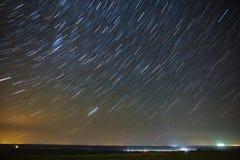 Отстаньте звезды вокруг приполюсной звезды накаляя над городом Стоковая Фотография