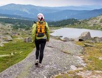 Отстаньте идущие по пересеченной местности женщины в горах на день лета красивый Стоковая Фотография