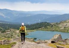 Отстаньте идущие по пересеченной местности женщины в горах на день лета красивый Стоковые Изображения