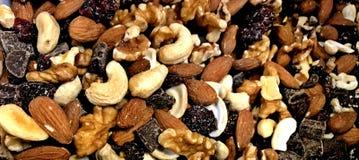 Отстаньте смешивание, анакардии, миндалины, грецкие орехи, изюминки, и темный шоколад стоковые изображения