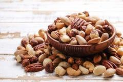 Отстаньте смешивание с различными видами гаек в коричневом деревянном шаре на поцарапанной белой предпосылке деревянного стола, м стоковые изображения rf