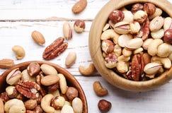 Отстаньте смешивание с различными видами гаек в коричневом деревянном шаре на поцарапанной белой предпосылке деревянного стола, м стоковые фото
