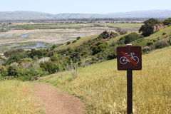 Отсутствие велосипед знака на холмистом trailhead Стоковое фото RF