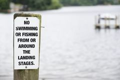 Отсутствие заплывание или рыбная ловля на столбе знака озера на деревянной пристани молы стоковое изображение rf
