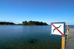 Отсутствие знака опасности заплывания на деревянной пристани где-то в Европе Стоковые Изображения RF