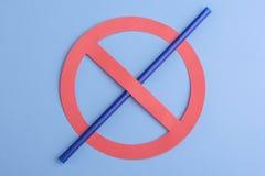 Отсутствие пластмассы Небольшая голубая солома в знаке запрета над голубой предпосылкой, показывая знак никакой пластиковой солом стоковая фотография