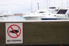 Отсутствие предупредительного знака рыбной ловли на блоке деревянной скамьи для сидеть в пироге Стоковое фото RF