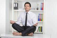 Отсутствие стресса. Уверенно бизнесмен сидя на столе офиса и стоковая фотография