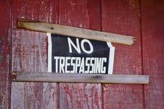 Отсутствие trespassing знака пригвозженного к экстерьеру дома Стоковые Фотографии RF