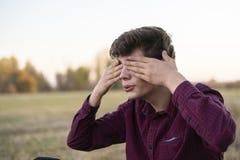 Отсчеты молодого человека играя прятк с глазами закрыли f стоковое фото