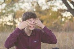 Отсчеты молодого человека играя прятк с глазами закрыли f стоковое изображение