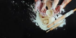 Отцы и руки детей режа печенье сердца от теста стоковая фотография rf