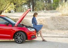 Отчаянная и confused женщина, который сели на мель на обочине с сломленными сбоем мотора автомобиля или аварией аварии Стоковое фото RF