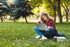 Отчаянная молодая женщина используя компьтер-книжку outdoors стоковая фотография