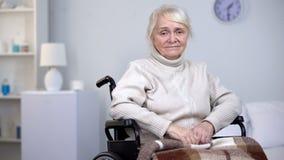 Отчаянная плача дама в кресло-коляске смотря в камеру, депрессию старости стоковое изображение rf