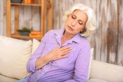 Отчаянная старшая дама имеет боль в сердце стоковые изображения